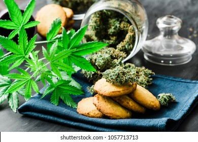 Cookies with buds cannabis and of marijuana on the table. A can of cannabis buds Concept of cooking with cannabis herb. Treatment of medical marijuana for use in food, On a black background use CBD