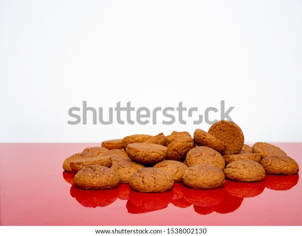 Cookies called pepernoten for the Dutch fest of Sinterklaas. On a red reflecting table against a white background.