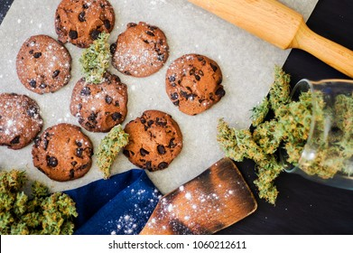 Cookies with cannabis and buds of marijuana on the table. top viewConcept of cooking with cannabis herb. Treatment of medical marijuana for use in food, On a black background top view CBD use