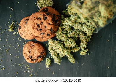Cookies with cannabis and buds of marijuana on the table. Copy Space Concept of cooking with cannabis herb. Treatment of medical marijuana for use in food, On a black background close up