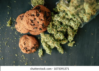 Cookies with cannabis and buds of marijuana on the table. Concept of cooking with cannabis herb. Treatment of medical marijuana for use in food, On a black background