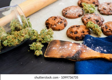 Cookies with cannabis and buds of marijuana on the table. Concept of cooking with cannabis herb. Treatment of medical marijuana for food use, On a black background CBD use