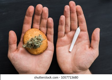 Cookies with cannabis and joint in hands, the concept of choosing the use of marijuana smoking or eating CBD Concept cooking vs cannabis herb. Treatment of medical marijuana for use in food