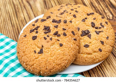 Cookies with chocolate on plate with kitchen towel on the table.