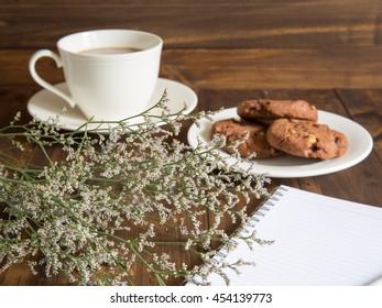 Cookies, coffee, flowers on wooden table