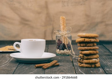 Cookies and coffee on the wooden table. Small depth of field and selective focus.