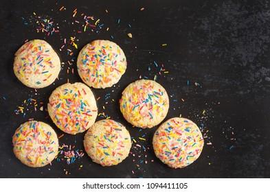 Cookies with colorful sprinkles on old black metal background, top view