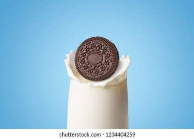 Cookies and cream of chocolate flavour with a sweet creme filling dropped in fresh milk splash in clear glass isolated on blue background (clipping path included), American famous snack brand