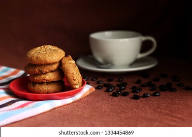 cookies with cups of hot coffee and coffee bean on a brown and loincloth fabric (The pattern on this fabric is common in Thailand and is not subjected to copyright)