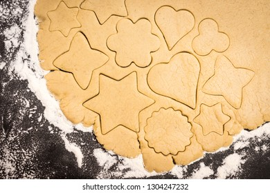 Cookies cut out of the dough, preparation before baking. Stars, heart, circle....