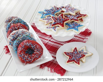 Cookies and donuts decorated with icing and sprinkles in red, blue, and white to celebrate 4th of July in America.