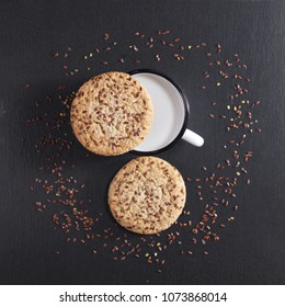 Cookies with flax seeds and sesame and enameled mug with milk on black stone background, top view. Selective focus