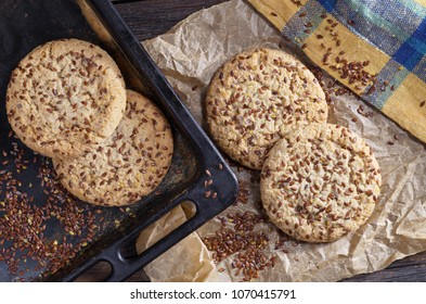 Cookies with flax seeds and sesame on baking tray on rustic wooden table with paper and napkin, top view