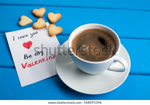 Cookies in the form of a heart with coffee on a blue wooden table. Valentine's Day.