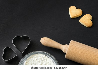 Cookies in heart shape lying after baking decorative with rolling pin and biscuit cutter