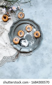 cookies with marmalade filling and icing sugar on a vintage plate