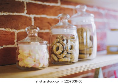 Cookies, marshmallows in glass jars on counter bar for sale.