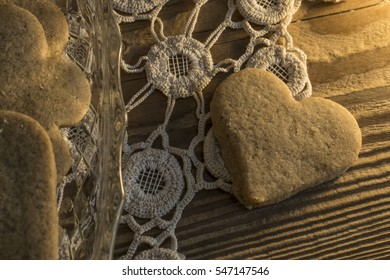 Cookies on Knitted tablecloth and wooden table. Two of them is white with powdered sugar and one with shape of heart