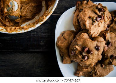 Cookies on a plate with cookie dough in a bowl