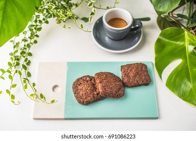 Cookies on a plate and a cup of coffee. Dessert close-up on white table. Healthy fresh vegetarian food.