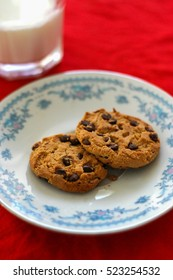 Cookies on a plate with a glass of milk on a red table cloth