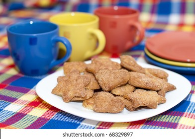 cookies on a plate with three cups and saucers