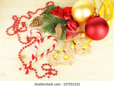 Cookies on ribbons with Christmas decorations on wooden table