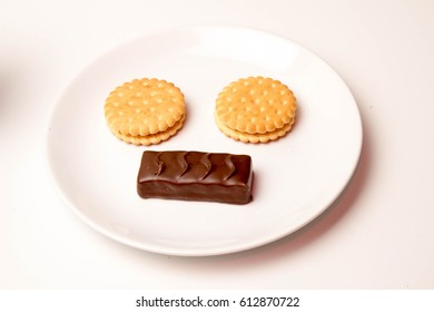 Cookies on a white plate with chocolate candies funny