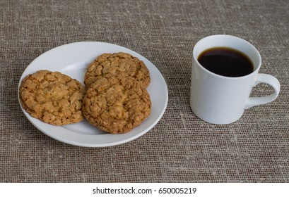 Cookies on a white plate and mug with coffee. Background of burlap.