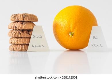 Cookies or orange fruit,  diet choice concept, calorie count
