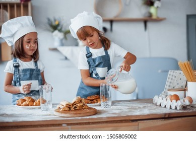 Cookies is ready. Family kids in white chef uniform preparing food on the kitchen.