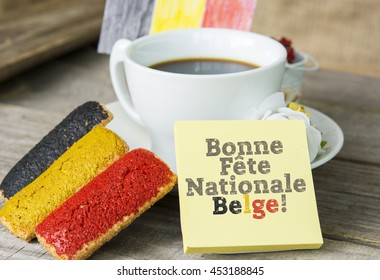 cookies with red black and yellow glaze as the Belgian flag colors. cup of coffee and a homemade flag of Belgium, decorative patriotic breakfast National Day of belgium text