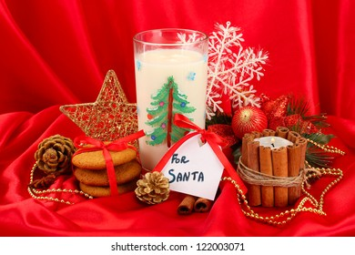 Cookies for Santa: Conceptual image of ginger cookies, milk and christmas decoration on red background