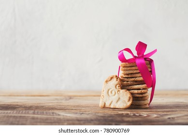 Cookies of shape heart with pink ribbon on wooden table