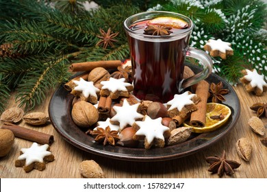 cookies in the shape of stars, spices and mulled wine on a plate, horizontal