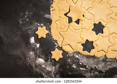 Cookies stars cut out of the dough, preparation before baking. Top view.