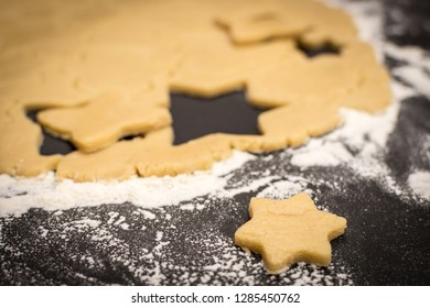 Cookies stars cut out of the dough, preparation before baking. Shallow depth of field.