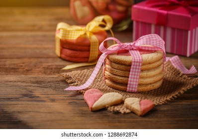 Cookies for Valentine's Day with pink ribbon on wooden table