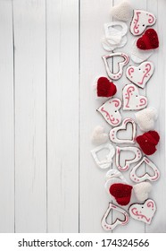 Cookies in white glaze and knit scarlet heart on a wooden background, side border.