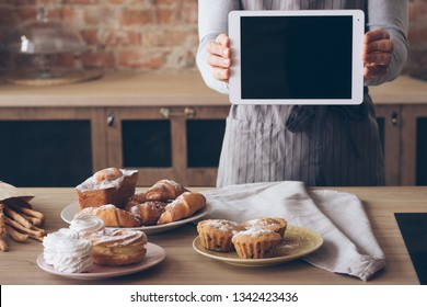 Cooking advertisement. Culinary class. Man in apron with black screen tablet. Fresh cakes and pastries assortment.
