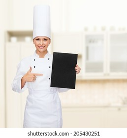 cooking, advertisement and food concept - smiling female chef pointing finger to blank black paper