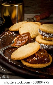 Cooking alfajores - a traditional dessert from Latin America or Mexico. Shortbread cookies with dulce de leche and coconut