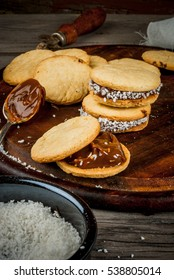 Cooking alfajores - a traditional dessert from Latin America or Mexico. Shortbread cookies with dulce de leche and coconut.
