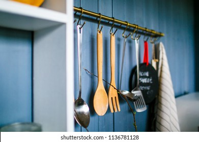 Cooking appliances on metal hooks in the kitchen