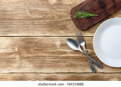 Cooking background concept. Vintage cutting board, plate and cutlery. Top view with copy space.