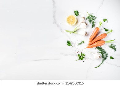 Cooking background with Fresh Vegetables for healthy dinner; carrots, herbs, olive oil, garlic; white marble background flat lay