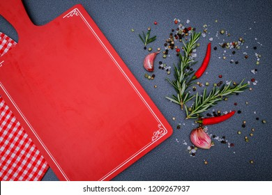 Cooking background with green Rosemary twig and red hot chili pepper and Red kitchen cutting Board on dark  background, copy space, text place.