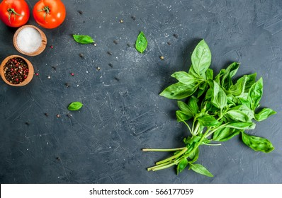 Cooking background. Kitchen table with spices (salt and pepper) and fresh basil, tomatoes, top view, copy space.