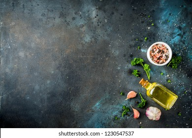 Cooking background with spices, olive oil and herbs, dark blue concrete background, copy space top view