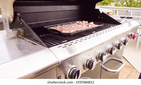 Cooking bacon stips on an outdoor gas grill.